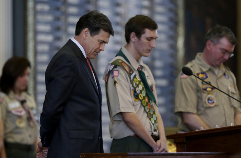 Gov. Rick Perry, left, bows his head for the invocation during the annual Boy Scouts Parade and Report to State in the House Chambers at the Texas State Capitol, Saturday, Feb. 2, 2013, in Austin, Texas. Perry says he hopes the Boy Scouts of America doesn't move soften its mandatory no-gays membership policy. (AP Photo/Eric Gay)