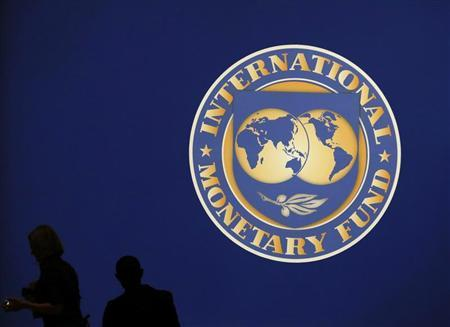 Visitors are silhouetted against the logo of the International Monetary Fund (IMF) in Tokyo