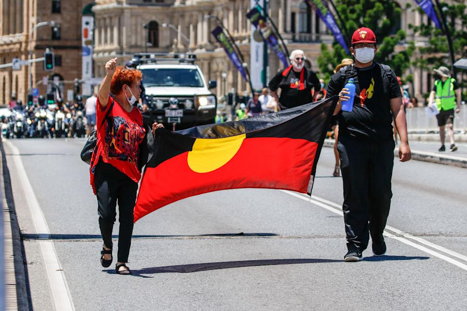 Protesters hold the Aboriginal Flag across Victoria Bridge during an Invasion Day rally in Brisbane.