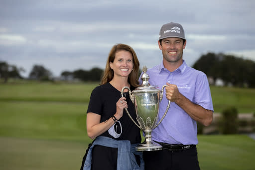 Robert Streb, right, and his wife Maggie Streb hold the trophy after a winning a second hole playoff against Kevin Kisner at the RSM Classic golf tournament, Sunday, Nov. 22, 2020, in St. Simons Island, Ga. (AP Photo/Stephen B. Morton)