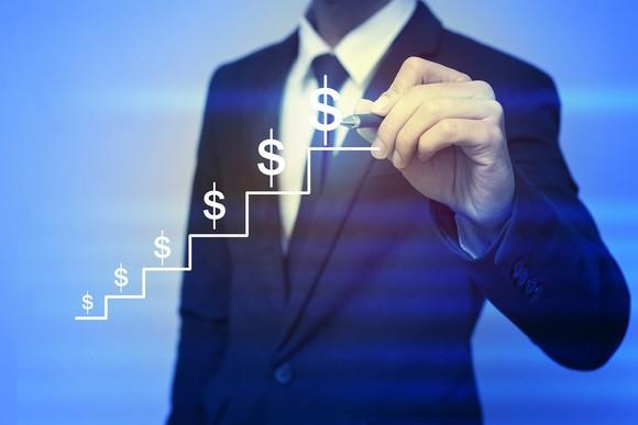 Dollar signs climbing up steps with businessman standing in the background.