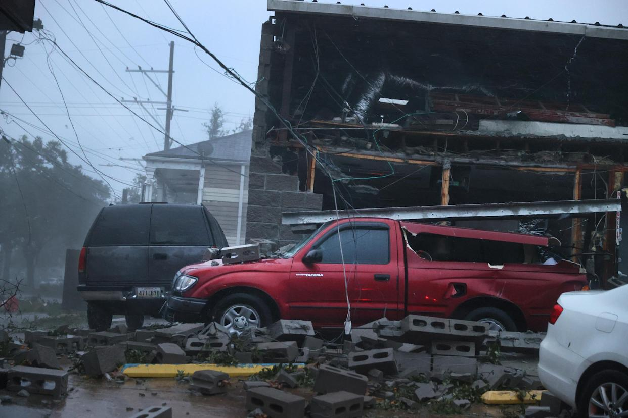 Damaged vehicles next to a partially collapsed building.