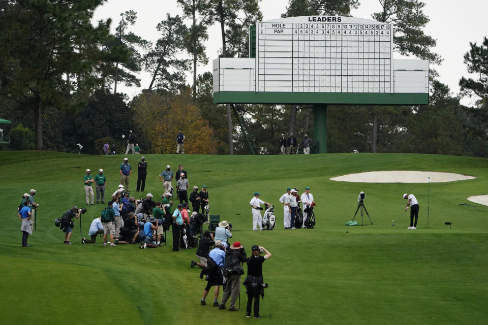 With no spectators in attendance, members of media and officials watch as Tiger Woods tees off on the third hole during a practice round for the Masters golf tournament Wednesday, Nov. 11, 2020, in Augusta, Ga. (AP Photo/Matt Slocum)