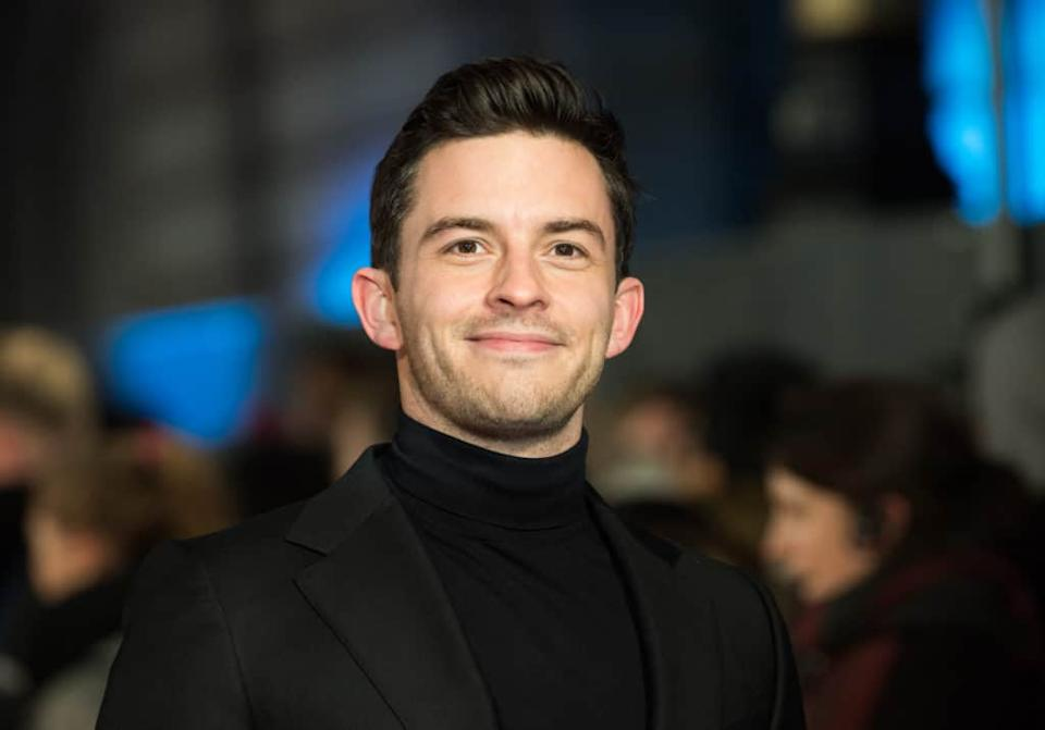 Jonathan Bailey smiles while wearing a black turtleneck and blazer