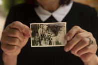 Samira Dajani holds a photo of her family in 1956 after they moved into their home in the Sheikh Jarrah neighborhood of east Jerusalem, Sunday, May 9, 2021. The Dajanis are one of several Palestinian families facing imminent eviction in the Sheikh Jarrah neighborhood of east Jerusalem. The families' plight has ignited weeks of demonstrations and clashes in recent days between protesters and Israeli police. (AP Photo/Maya Alleruzzo)