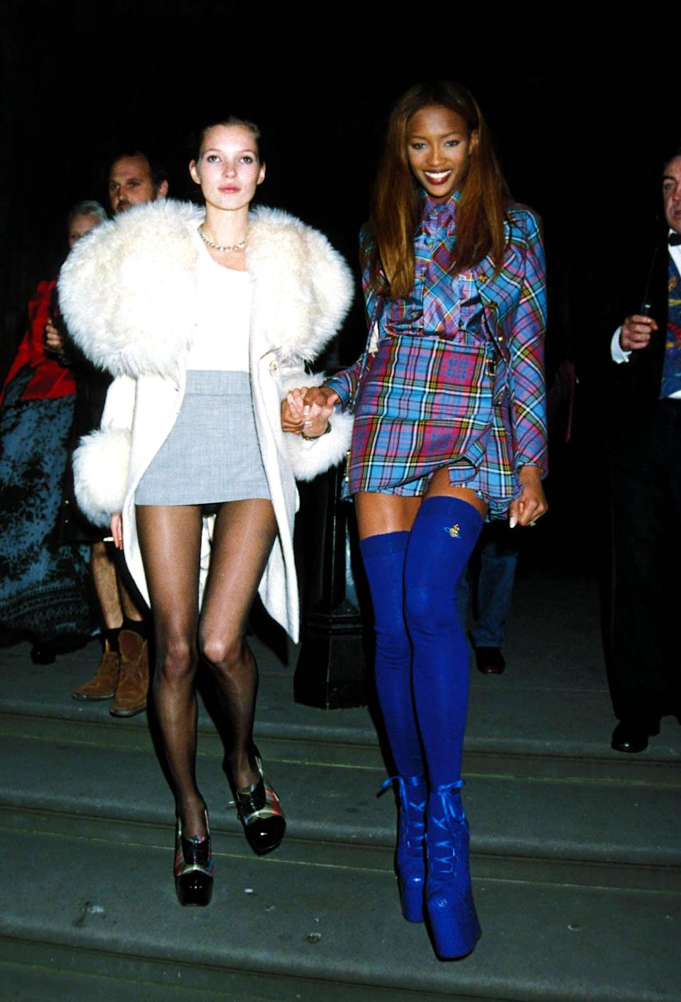 """<p>Models <a class=""""link rapid-noclick-resp"""" href=""""https://www.popsugar.com/Kate-Moss"""" rel=""""nofollow noopener"""" target=""""_blank"""" data-ylk=""""slk:Kate Moss"""">Kate Moss</a> and <a href=""""https://www.popsugar.com/fashion/Naomi-Campbell-Runway-Photos-46531324"""" class=""""link rapid-noclick-resp"""" rel=""""nofollow noopener"""" target=""""_blank"""" data-ylk=""""slk:Naomi Campbell"""">Naomi Campbell</a> were a stylish force to be reckoned with at London Fashion Week in 1993. Moss paired her statement fur-trimmed coat with a white blouse and gray miniskirt while Campbell punched up her plaid dress with electric blue thigh-high socks and platform shoes. </p>"""