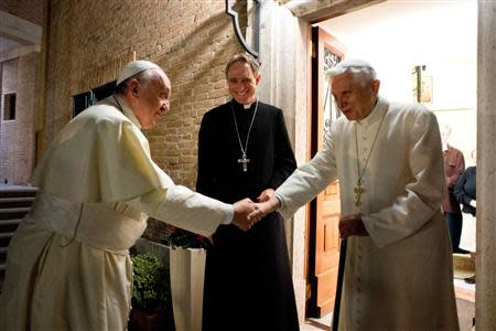 Pope Francis (L) shakes hands with Pope Emeritus Benedict XVI at the Mater Ecclesiae monastery at the Vatican, December 23, 2013. REUTERS/Osservatore Romano