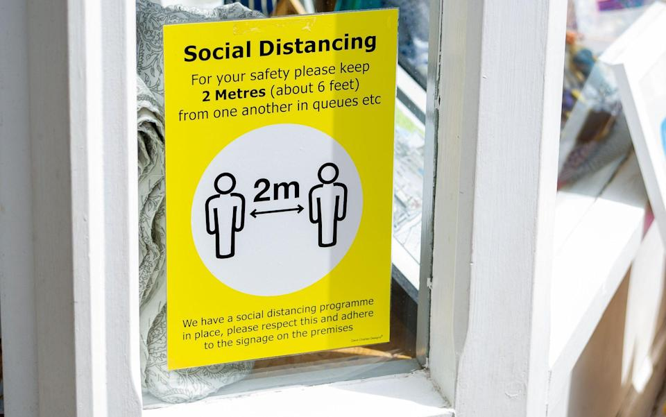 A sign in the window telling people to stay two metres away from each other inside a shop in Hertfordshire - Maureen McLean/Shutterstock