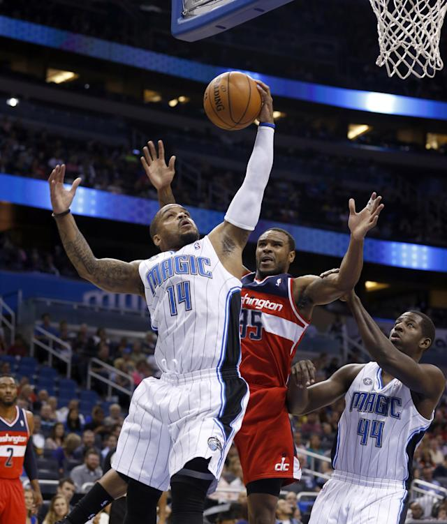 Orlando Magic forward Andrew Nicholson (44), of Canada, assists Jameer Nelson (14) who fights for a rebound against Washington Wizards forward Trevor Booker (35) during the first half of an NBA basketball game in Orlando, Fla., Friday, April 11, 2014. (AP Photo/Reinhold Matay)