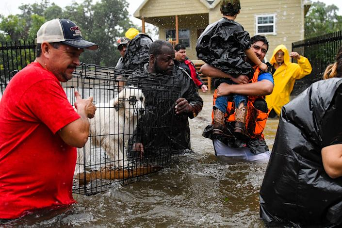 Volunteers and first responders help flood victims evacuate to shelters as waters rise from Hurricane Harvey on Aug 28, 2017, in Houston.