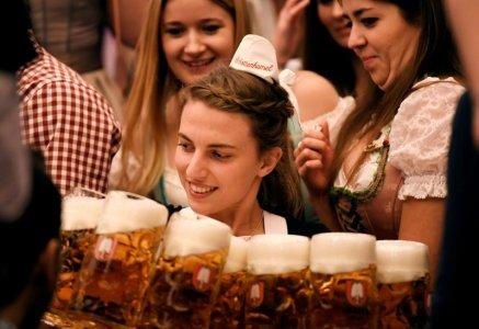 FILE PHOTO: A waitress carries mugs of beer during the opening day of the 185th Oktoberfest in Munich, Germany September 22, 2018. REUTERS/Andreas Gebert/File Photo