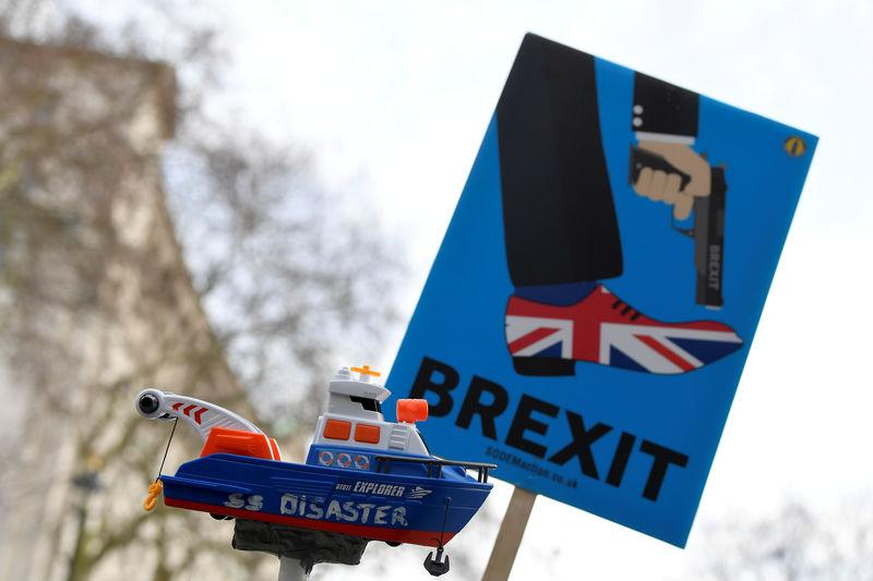 FILE PHOTO: Anti-Brexit protesters hold up a sign and a model prop boat outside Downing Street in London