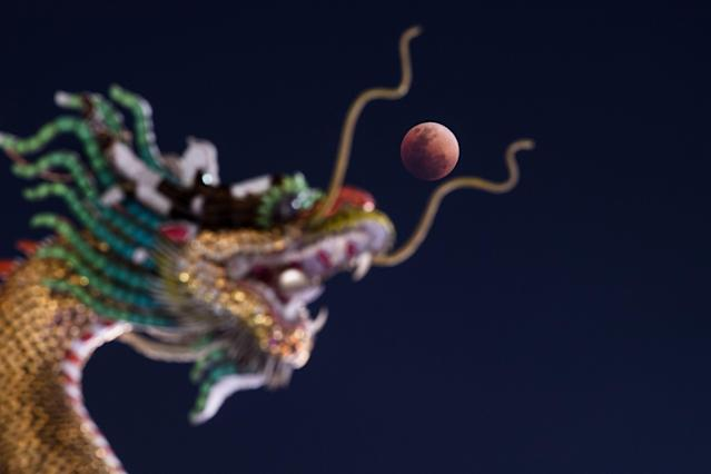 <p>The moon rises over the horizon above the head of a Chinese dragon statue at a Buddhist temple in Bangkok on Jan. 31, 2018. (Photo: Roberto Schmidt/AFP/Getty Images) </p>