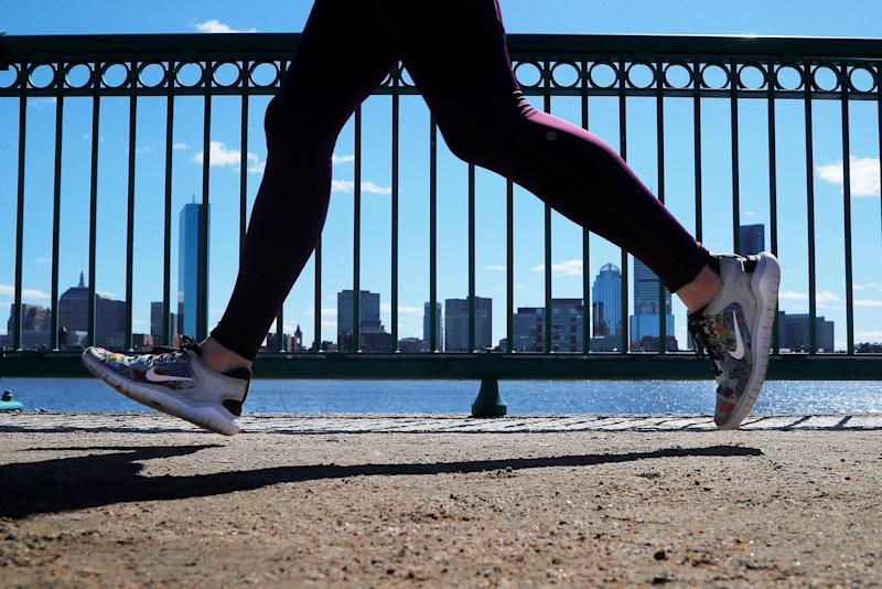 A jogger wearing Nike shoes runs past the Boston skyline along the Charles River in Cambridge, Massachusetts, U.S., March 18, 2019. REUTERS/Brian Snyder