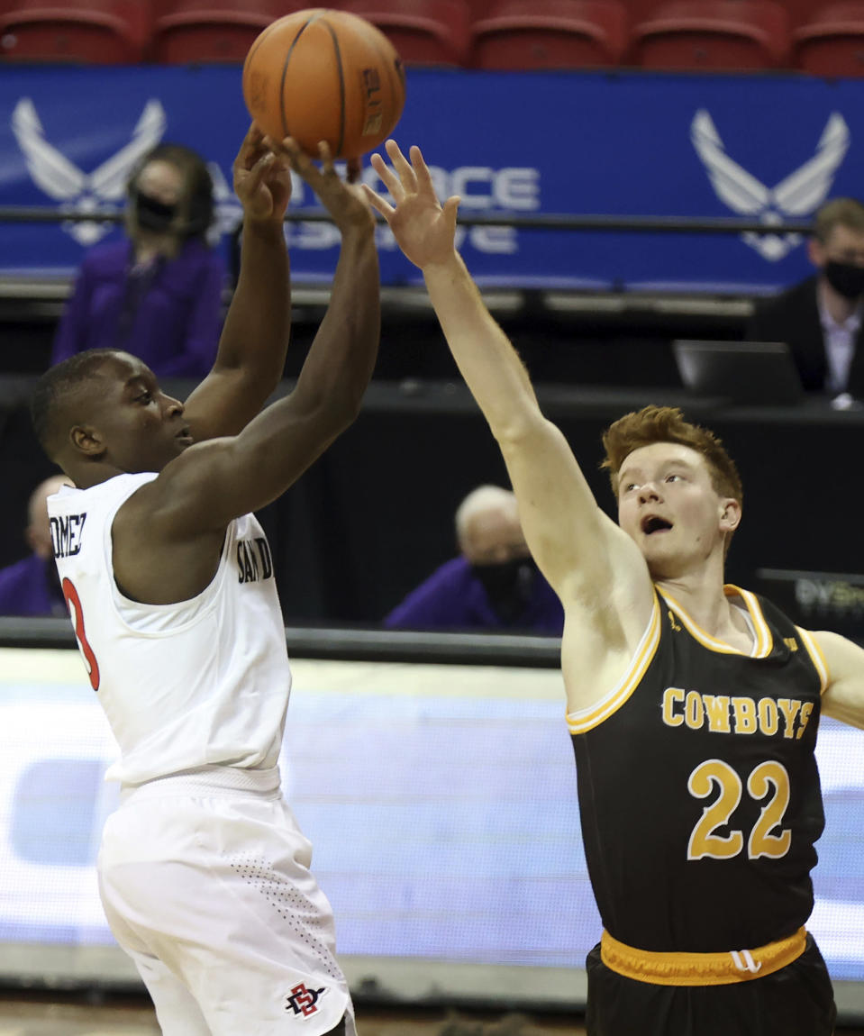San Diego State guard Terrell Gomez (3) shoots over Wyoming guard Kenny Foster (22) during the first half of an NCAA college basketball game in the quarterfinal round of the Mountain West Conference tournament Thursday, March 11, 2021, in Las Vegas. (AP Photo/Isaac Brekken)