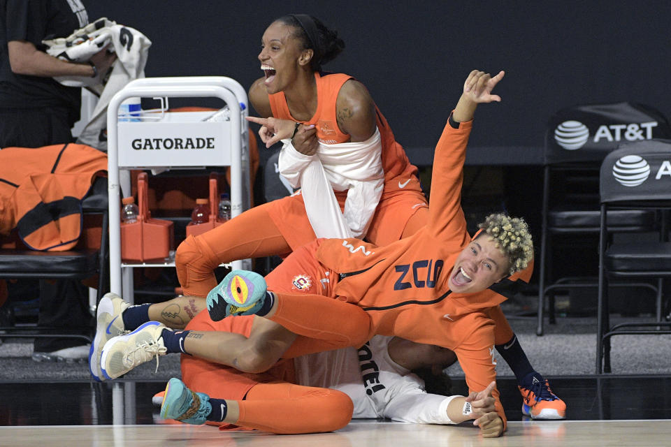 Connecticut Sun forward DeWanna Bonner, above, guard Natisha Hiedeman, center, and forward Theresa Plaisance celebrate after a successful three-point basket by guard Jasmine Thomas during the first half of Game 1 of a WNBA basketball semifinal round playoff game against the Las Vegas Aces, Sunday, Sept. 20, 2020, in Bradenton, Fla. (AP Photo/Phelan M. Ebenhack)