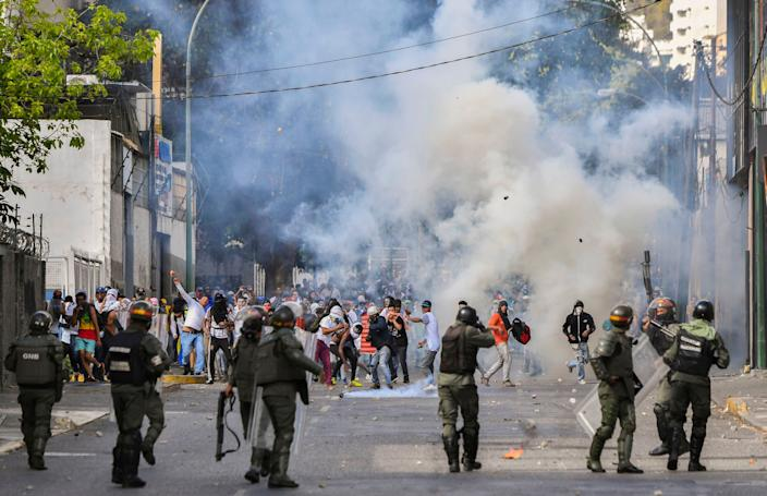 Riot police clash with opposition demonstrators during a protest against the government of President Nicolas Maduro in Caracas on Jan. 23, 2019.