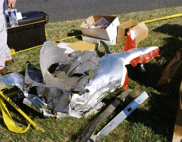 <p>Tangled metal from the plane lies on the grass (FBI) </p>