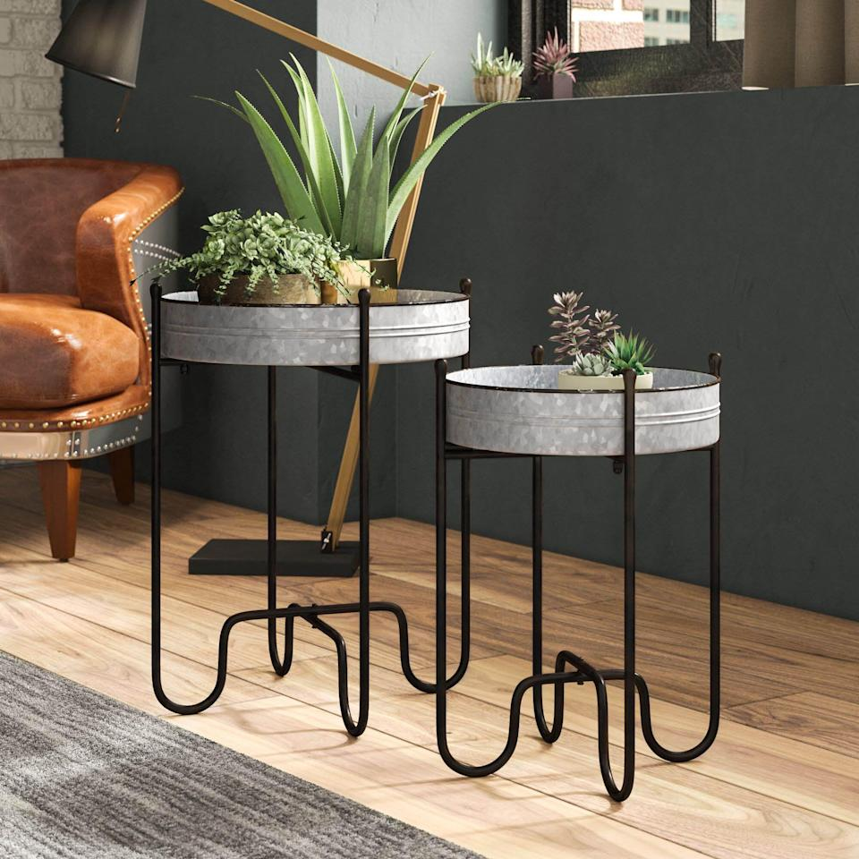 """<p><strong>Williston Forge</strong></p><p>wayfair.com</p><p><strong>$92.99</strong></p><p><a href=""""https://go.redirectingat.com?id=74968X1596630&url=https%3A%2F%2Fwww.wayfair.com%2Ffurniture%2Fpdp%2Fwilliston-forge-dilley-round-plant-stand-w004996468.html&sref=https%3A%2F%2Fwww.popularmechanics.com%2Fhome%2Fg36421088%2Fbest-plant-stands%2F"""" rel=""""nofollow noopener"""" target=""""_blank"""" data-ylk=""""slk:Shop Now"""" class=""""link rapid-noclick-resp"""">Shop Now</a></p><p>This eye-catching plant stand duo features galvanized metal tray tables set on distress black tubular frames for an edgy, industrial look. The larger stand has a 17-inch-wide tray and is just under 2 feet high, and the narrower stand is roughly 5 inches shorter with a 13-inch-wide tray. While the plant stands are intended for indoor use, you can use them on a covered porch <a href=""""https://www.popularmechanics.com/home/g36017483/best-pergolas/"""" rel=""""nofollow noopener"""" target=""""_blank"""" data-ylk=""""slk:or pergola"""" class=""""link rapid-noclick-resp"""">or pergola</a>—as long as they're kept out of the rain. </p>"""