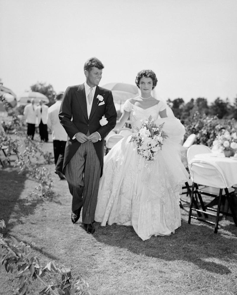 A scene from the Kennedy-Bouvier wedding. Groom John walks alongside his bride Jacqueline at an outdoor reception, 1953. Newport, Rhode Island. (Photo by Bachrach/Getty Images)
