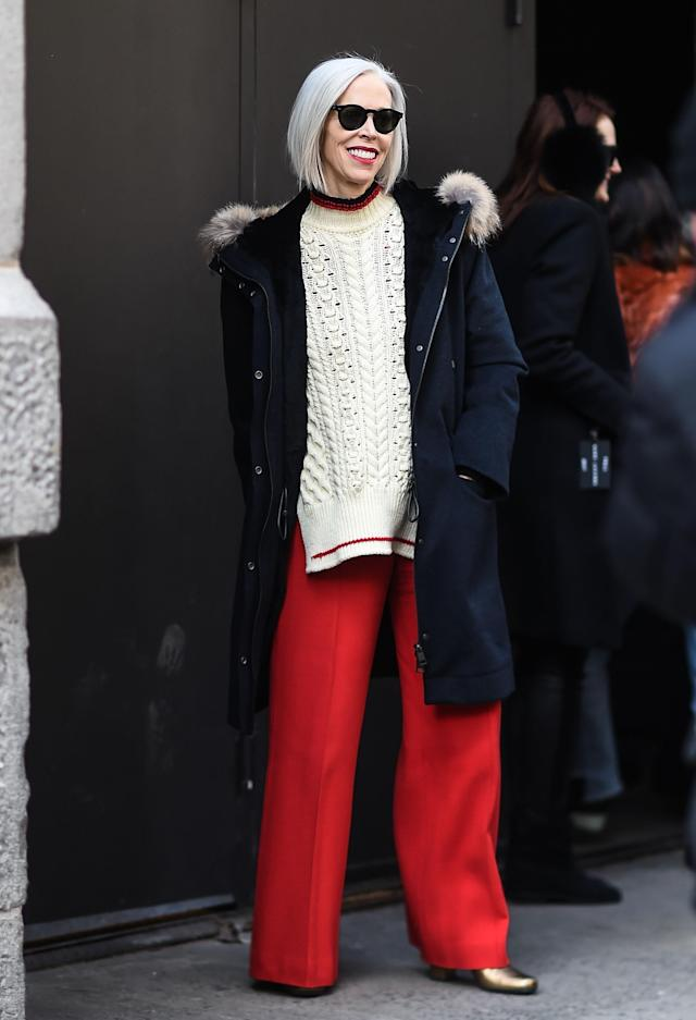 <p>Linda Fargo, fashion director at Bergdorf Goodman, wears a parka, cableknit sweater, bright red, wide-legged trousers, gold booties, and a chic pair of wayfarers. Whether you're 25 or 55, this is a great look for all. (Photo: Getty) </p>