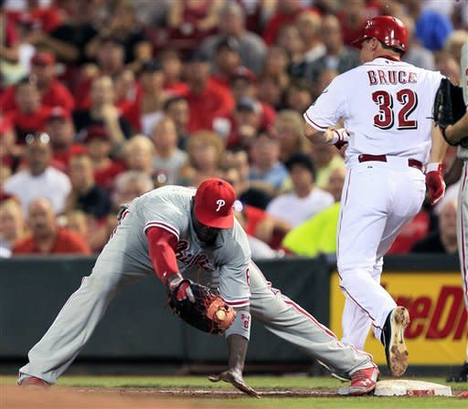 Cincinnati Reds' Jay Bruce (32) is safe at first with an infield single as Philadelphia Phillies first baseman Ryan Howard stretches for the throw in the fourth inning of a baseball game, Tuesday, Sept. 4, 2012, in Cincinnati. (AP Photo/Al Behrman)