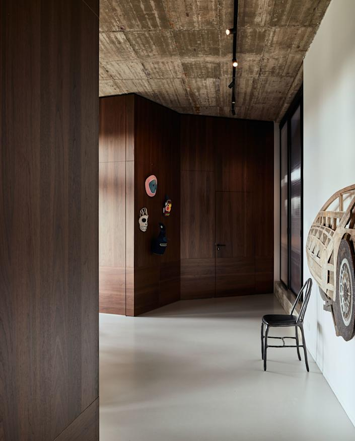 """<div class=""""caption""""> The kids' rooms are located one floor below the penthouse, on the top floor of the existing former office building. The space is characterized by its height—nearly 12 feet—and the <em>béton brut</em>, or raw concrete, ceiling. All rooms on this level are clad in American walnut. </div>"""