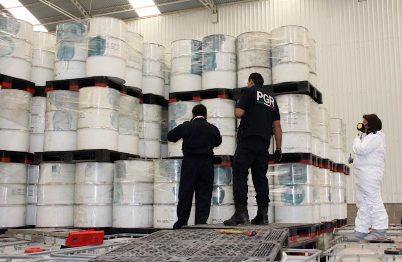 In this June 20, 2011, photo released by Mexico's Attorney General's office, police investigators look at drums of precursor chemicals for methamphetamine that were seized in Queretaro, Mexico. Mexican authorities have made two major busts in as many months in the quiet central state of Queretaro. In one case, they seized nearly 500 tons (450 metric tons) of precursor chemicals. Another netted 3.4 tons (3.1 metric tons) of pure meth, which at $15,000 a pound would have a street value of more than $100 million. Mexico's most powerful drug cartel appears to be expanding methamphetamine production on a massive scale, filling a gap left by the breakdown of a rival gang that was once the top trafficker of the synthetic drug.  (AP Photo/Attorney General's office)