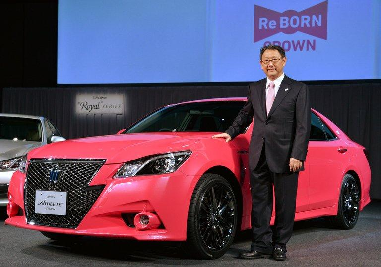 Akio Toyoda, president of Toyota, poses with the company's flagship Crown sedan in Tokyo on December 25, 2012