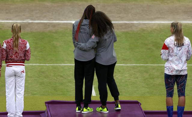 Serena Williams (center, R) and her sister Venus Williams, of the U.S., stand on the podium with their gold medals during the presentation ceremony for the women's doubles tennis at the All England Lawn Tennis Club during the London 2012 Olympic Games August 5, 2012. REUTERS/Adrees Latif (BRITAIN - Tags: OLYMPICS SPORT TENNIS TPX IMAGES OF THE DAY)