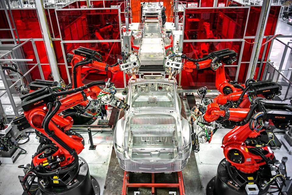 Cars move along a robotic assembly line at Tesla's factory in Fremont.