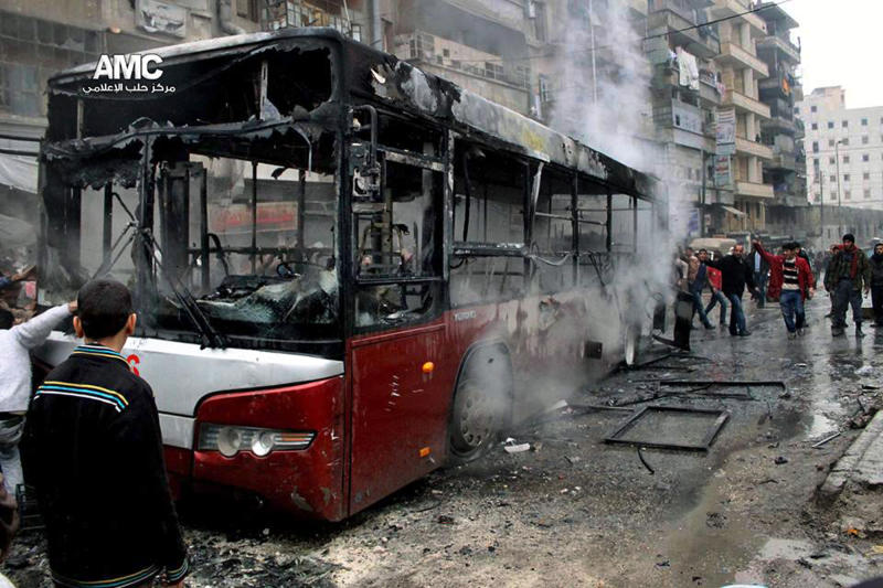 This image provided by Aleppo Media Center AMC which has been authenticated based on its contents and other AP reporting, shows Syrians inspecting a burnt bus after a missile fired by Syrian government aircraft hit the vehicle in the rebel-held neighborhood of al-Bab in Aleppo, Syria, Tuesday, Dec. 31, 2013. The bus was full of people when it was struck, setting it on fire and killing several people, activists said.. (AP Photo/Aleppo Media Center AMC)