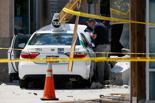 "<p>An official photographs the scene where police say a taxi driver struck a group of pedestrians, injuring several, Monday, July 3, 2017, in Boston. A police official said the crash is believed to be a case of ""operator error"" in which the driver stepped on the gas pedal instead of the brake. (AP Photo/Michael Dwyer) </p>"