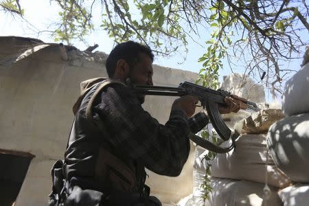 Fighter from the Free Syrian Army's Al Rahman legion fires his weapon on the frontline against the forces of Syria's President Assad in Jobar, a suburb of Damascus, Syria