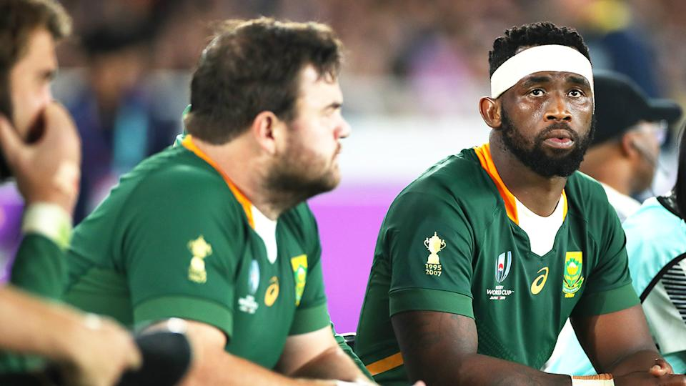 Siya Kolisi (pictured right) looks on from the bench during the Rugby World Cup 2019 Final.