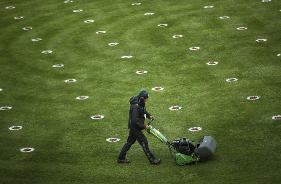 A member of the grounds staff cuts the grass dotted with social distance markers in the parade ring before the start of the Liverpool NHS Day of the 2021 Grand National Festival at Aintree Racecourse in Liverpool, England, Thursday April 8, 2021. The Aintree Grand National 2021 is a the three day festival of horse racing first run in 1839.(Tim Goode/PA via AP)