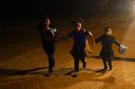 Three young migrants hold hands as they run in the rain at an intake area after turning themselves in upon crossing the U.S.-Mexico border Tuesday, May 11, 2021, in Roma, Texas. The number of unaccompanied children encountered on the U.S. border with Mexico in April eased from an all-time high a month earlier, while more adults were found coming without families, authorities said Tuesday. (AP Photo/Gregory Bull)