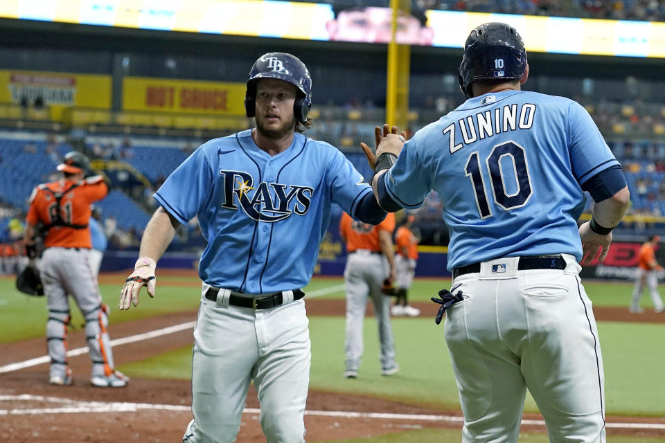 Tampa Bay Rays' Brett Phillips and Mike Zunino (10) celebrate after scoring on a two-run double by Brandon Lowe off Baltimore Orioles pitcher Jorge Lopez during the fourth inning of a baseball game Saturday, June 12, 2021, in St. Petersburg, Fla. (AP Photo/Chris O'Meara)