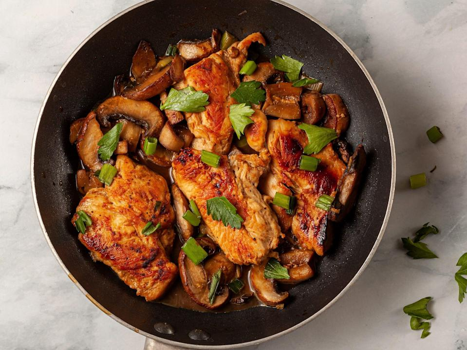 A nonstick frying pan with a chicken breast sautee inside. Meat is seasoned with herbs, tomato, spices, parsley, spring onions and mushrooms.