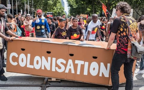 A group of Aboriginals stand in front of a a mock coffin with 'Colonisation' written on it on Australia Day - Credit: Anadolu Agency
