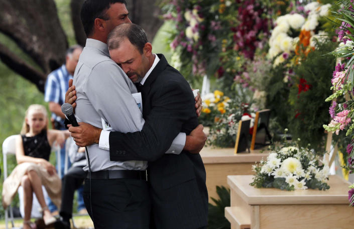Men embrace next to the coffins of Dawna Ray Langford, 43, and her sons Trevor, 11, and Rogan, 2, who were killed by drug cartel gunmen, during the funeral at a family cemetery in La Mora, Sonora state, Mexico, Thursday, Nov. 7, 2019. Three women and six of their children, all members of the extended LeBaron family, died when they were gunned down in an attack while traveling along Mexico's Chihuahua and Sonora state border on Monday. (AP Photo/Marco Ugarte)