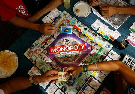 Players participate in a Guinness world record attempt taking place across the world for the largest simultaneous game of Monopoly, at a hotel in Madrid, August 27, 2008. REUTERS/Paul Hanna/File Photo