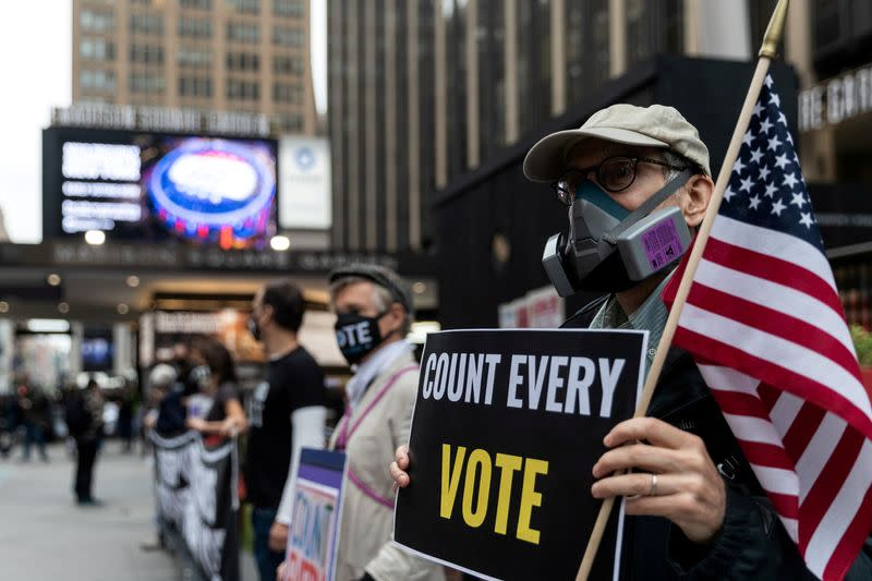 FILE PHOTO: Voters line up to cast ballots on the first day of early voting in New York