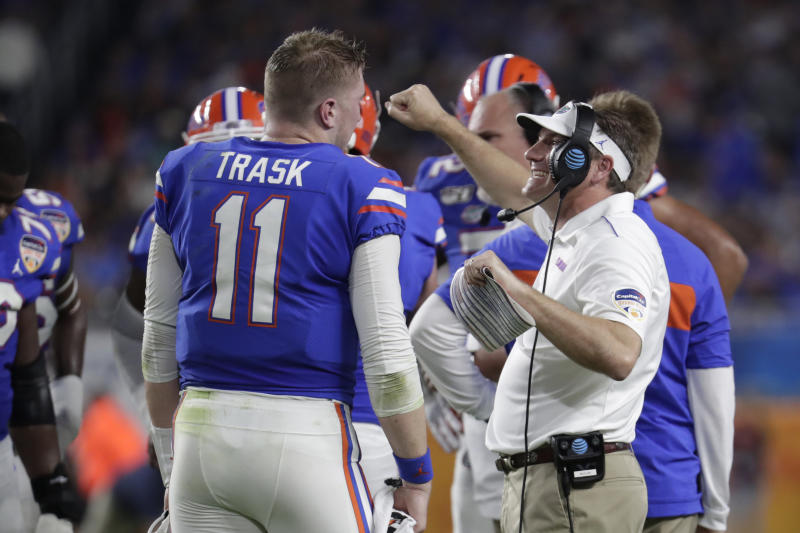 Florida head coach Dan Mullen, right, talks with quarterback Kyle Trask (11) during the first half of the Orange Bowl NCAA college football game against Virginia, Monday, Dec. 30, 2019, in Miami Gardens, Fla. (AP Photo/Lynne Sladky)