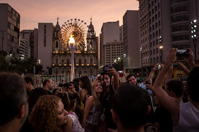 <p>People take photographs in front of the Olympic flame outside the Candelaria Church on August 6, 2016 in Rio de Janeiro, Brazil. People visited the flame on the opening day of the Rio 2016 Olympic Games starting seventeen days of competition. (Photo by Chris McGrath/Getty Images) </p>