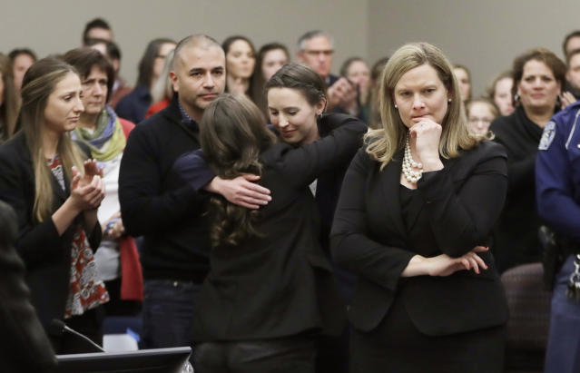 Former gymnast Rachael Denhollander, center, is hugged after giving her victim impact statement during the seventh day of Larry Nassar's sentencing hearing. (AP)