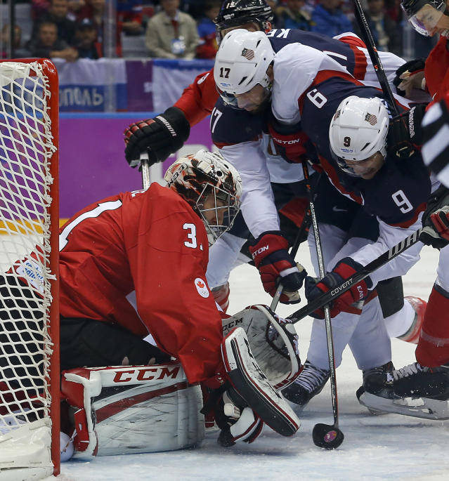 USA forward Zach Parise (9) tries to score against Canada goaltender Carey Price during the first period of a men's semifinal ice hockey game at the 2014 Winter Olympics, Friday, Feb. 21, 2014, in Sochi, Russia. (AP Photo/Julio Cortez)