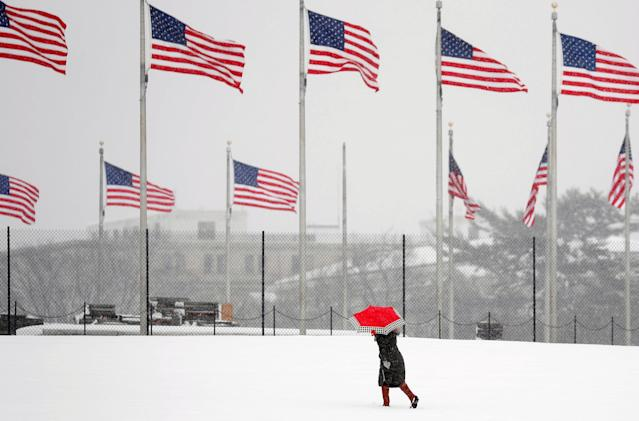 A woman holds an umbrella as she walks toward the Washington Monument during a snowstorm in Washington, U.S., March 21, 2018. REUTERS/Kevin Lamarque TPX IMAGES OF THE DAY
