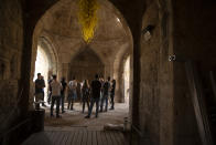 A group gathers under a work by American sculptor Dale Chihuly at the Tower of David Museum in the Old City of Jerusalem, Wednesday, Oct. 28, 2020. The ancient citadel is devoid of tourists due to the pandemic and undergoing a massive restoration and conservation project. (AP Photo/Maya Alleruzzo)