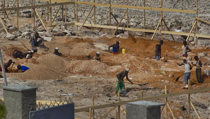 FILE - In this Wednesday, April 24, 2013 file photo, laborers work in the sun on a construction project near the airport in Mogadishu, Somalia. Despite the occasional militant attack, this seaside city's real estate market has seen an upsurge in demand over the last two years, thanks in part to security gains made following the ouster of the al-Qaida-linked Islamic rebels of al-Shabab. (AP Photo/Ben Curtis, File)